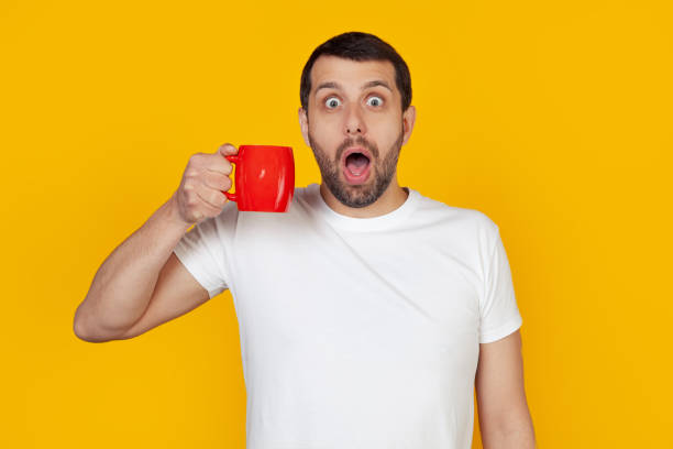 Young man with a beard in a white t-shirt drinks a cup of coffee, scared in shock with a surprised face, scared and excited with an expression of fear. Stands on isolated yellow background stock photo