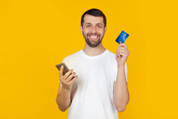 Young man with a beard in a white t-shirt holding a credit card. by credit card to pay online using a smartphone. Stands on isolated yellow background stock photo