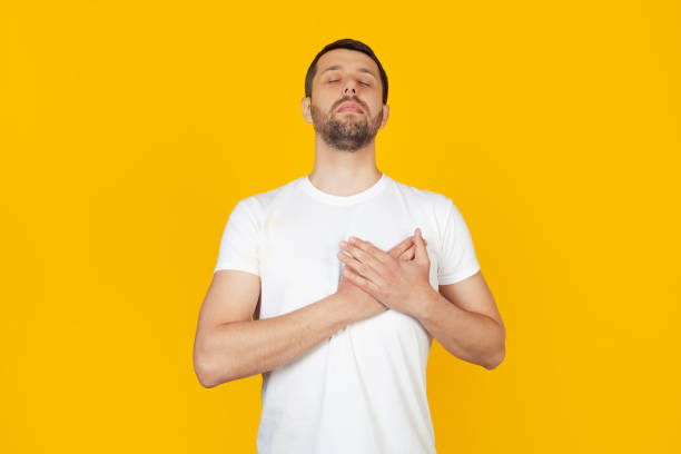 Young man with a beard in a white T-shirt smiling, putting his hands on his chest with closed eyes and a grateful gesture on his face. Health concept. Stands on isolated yellow background. stock photo