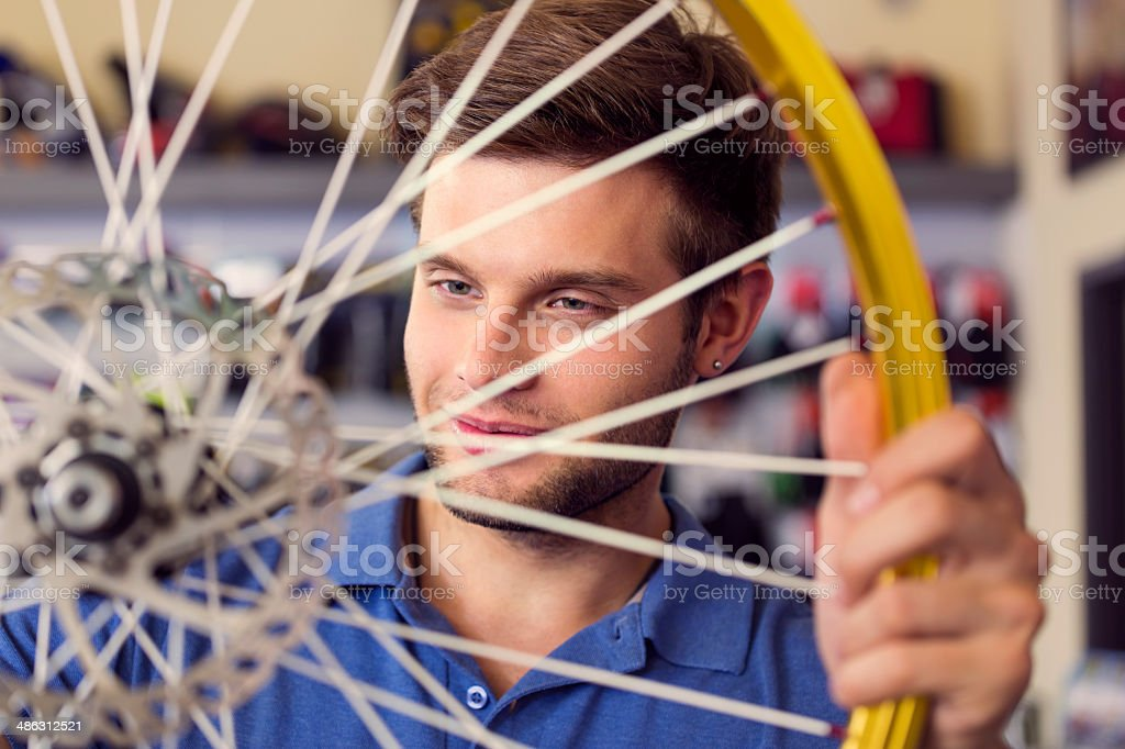 Young man with a bicycle wheel Portrait of young sales clerk in a bike store looking at bicycle wheel. 20-24 Years Stock Photo