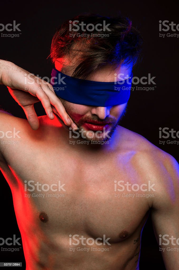 Young man with a blindfold around the eyes stock photo