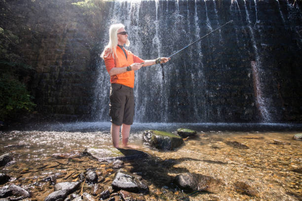 Young man with a blonde hair and beard in waterfall nature enviroment stock photo