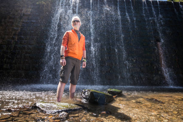 Young man with a blonde hair and beard posing for a camera in front of a waterfall stock photo