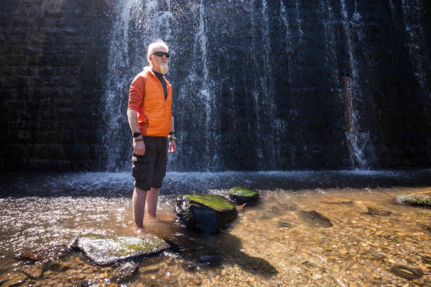 Young man with a blonde hair and beard standing in front of a waterfall stock photo