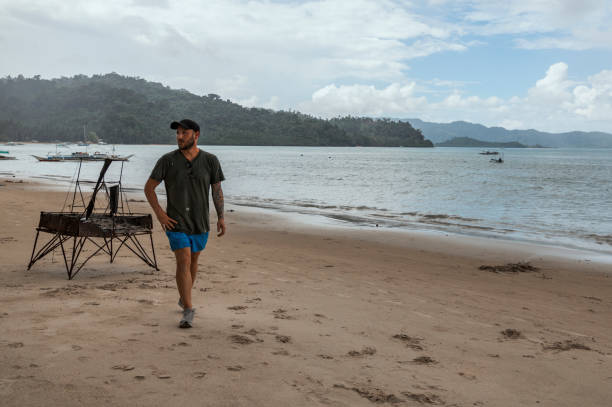 A young man with a cap and a swimswit takes a walk on the beach of Port Barton, Palawan, Philippines stock photo