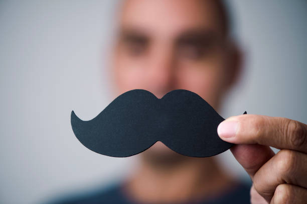 young man with a fake moustache closeup of a young caucasian man holding a fake moustache in front of his face mustache stock pictures, royalty-free photos & images
