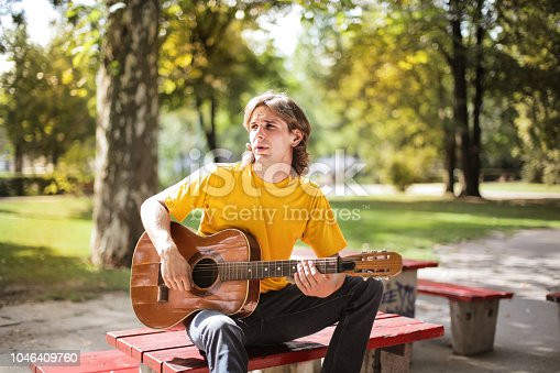 Young man with a guitar hanging out in a park