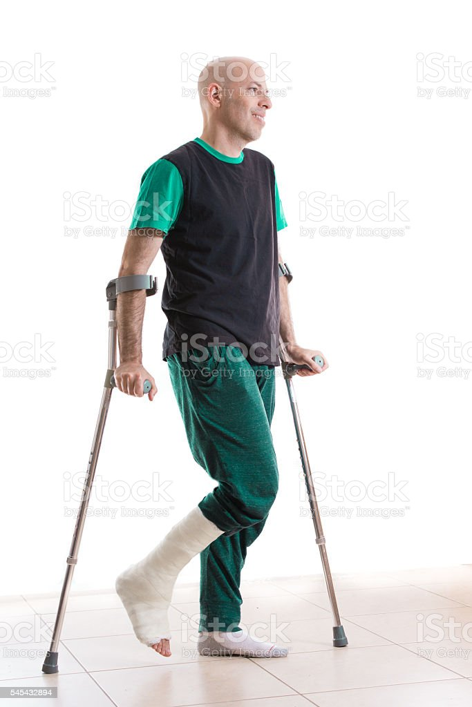 Young man with a leg cast and crutches stock photo