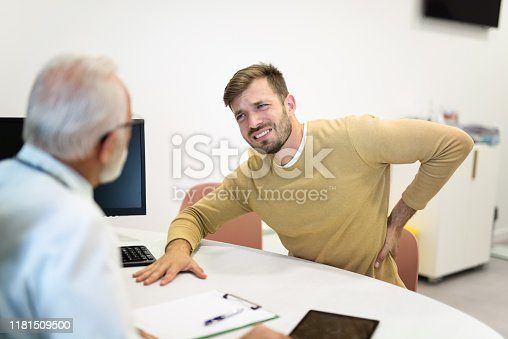 885281276istockphoto Young man with a painful back on a medical exam. 1181509500