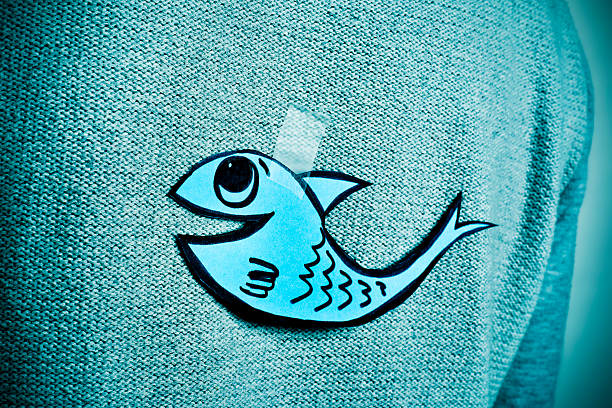 young man with a paper fish attached to his back closeup of a young man with a paper fish attached with tape to his back, with a slight vignette added april fools day stock pictures, royalty-free photos & images