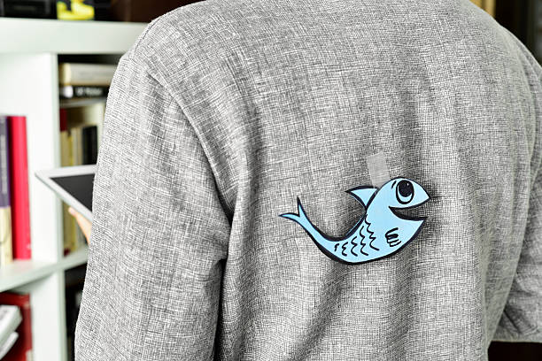 young man with a paper fish attached to his back - april fools stock photos and pictures