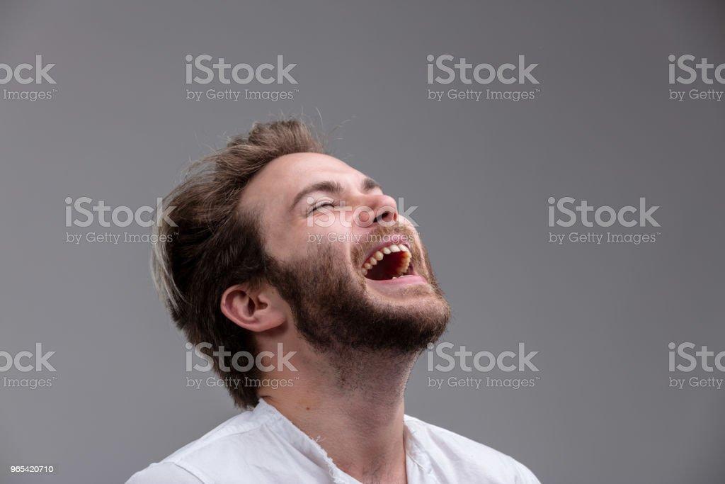 Young man with a sense of humour enjoying a laugh zbiór zdjęć royalty-free