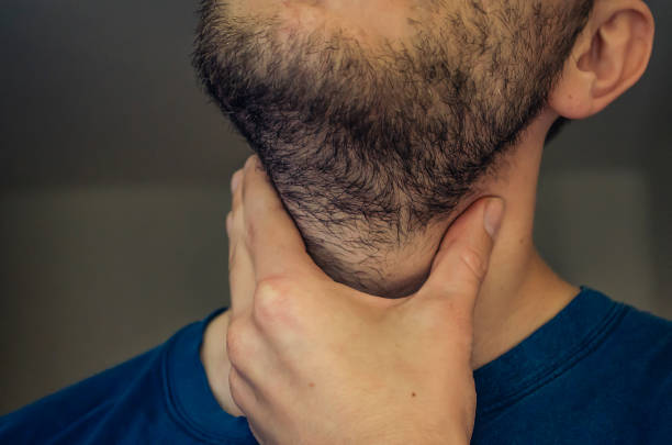 A young man with a sore throat. A young man with a sore throat. With his hand on the neck, sharp pain in the throat. Close up. throat stock pictures, royalty-free photos & images