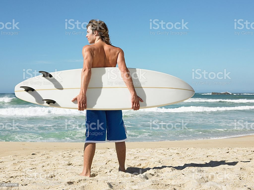 Young man with a surfboard stock photo