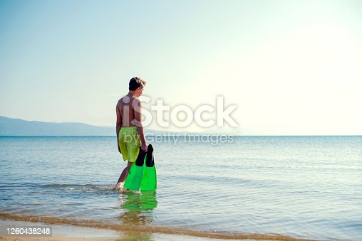 Young man with a swimming fin going into sea