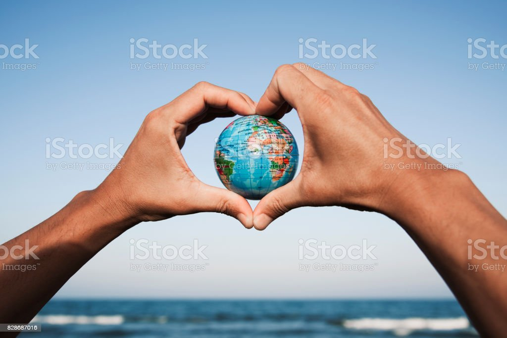 young man with a world globe in his hands stock photo