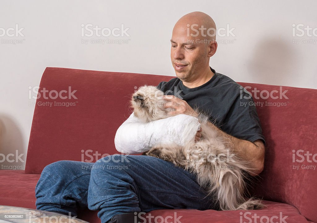 Young man with an arm cast petting his cat stock photo