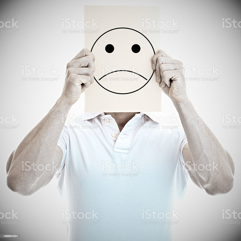 Young man with an unhappy smiley card covering face stock photo