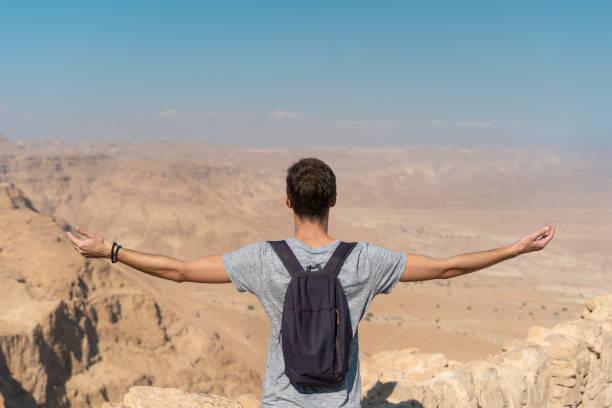 jonge man met armen verhoogd kijken naar het panorama over de woestijn in israël - israël stockfoto's en -beelden