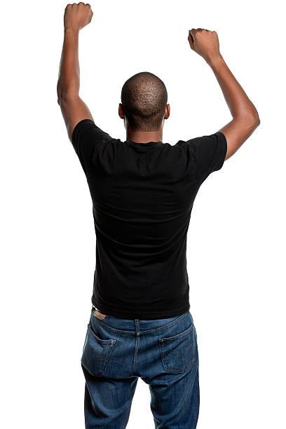 junger mann mit arme hoch, schütteln der faust, rückansicht - arme hoch stock-fotos und bilder