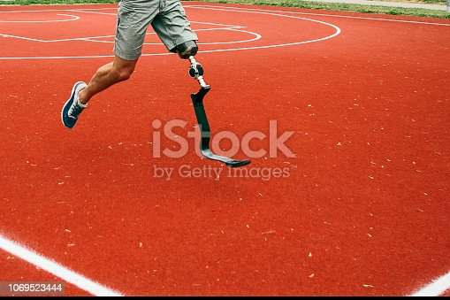 Young man with artificial limb running fast