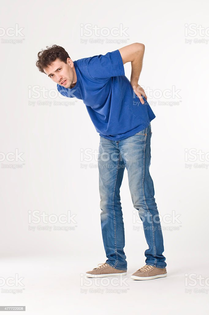 Young man with back pain. stock photo