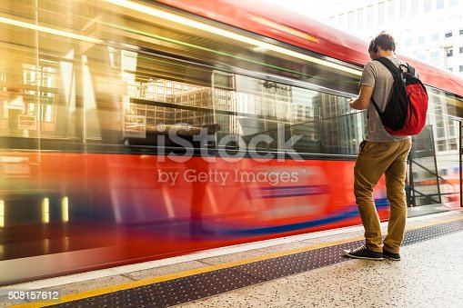 istock Young man with backpack and headphones waiting for train 508157612
