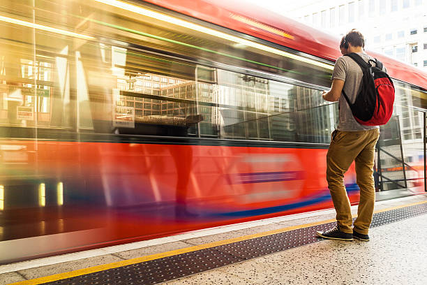 Young man with backpack and headphones waiting for train A photo of a young man wearing headphones while waiting for the train. He is on the right side of the image, and a red train is moving in front of him. The train has long windows that reflect the buildings in front of them. The middle section of the train is moving in a blur. There are truncated domes on the sidewalk between the man and the train. The man has short brown hair, and his headphones are black. He is wearing a gray short-sleeved shirt, tan-colored pants, black sneakers and a red and black backpack. A building with many windows is on the other side of the train. The man is holding a smartphone and is looking intently at its screen. subway platform stock pictures, royalty-free photos & images