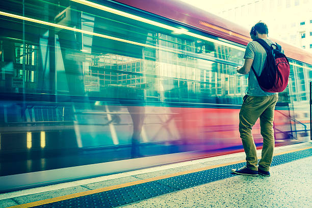 Young man with backpack and headphones waiting for train stock photo