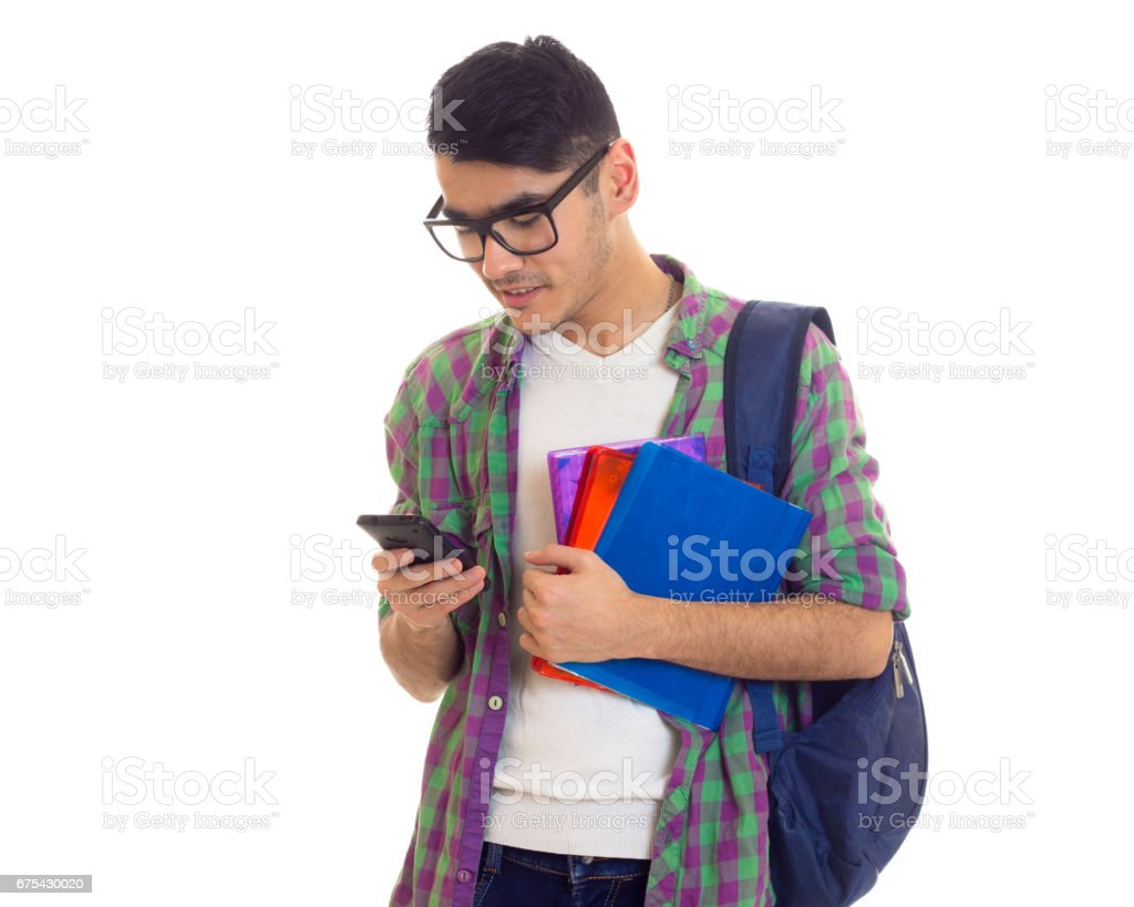 Young man with backpack, smartphone and books photo libre de droits