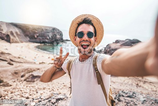 istock Young man with backpack taking selfie portrait on a mountain - Smiling happy guy enjoying summer holidays at the beach - Millennial showing victory hands symbol to the camera - Youth and journey 1329031407