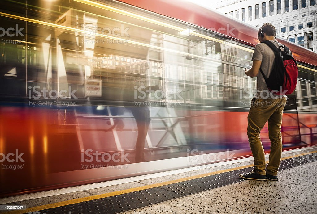 Young man with backpack waiting for train stock photo
