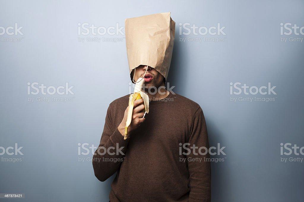 Young man with bag over head eating banana stock photo