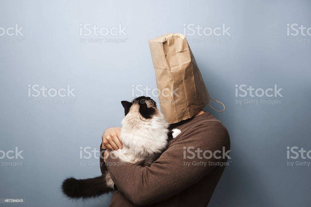 Young man with bag over head holding his cat stock photo