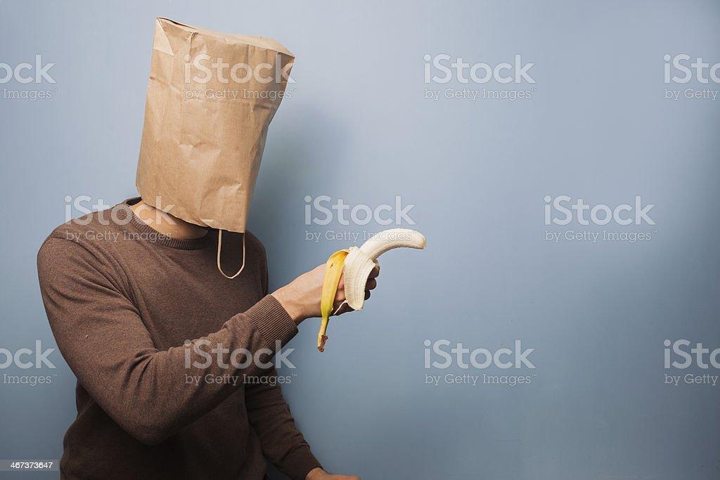 Young man with bag over head using banana as gun stock photo