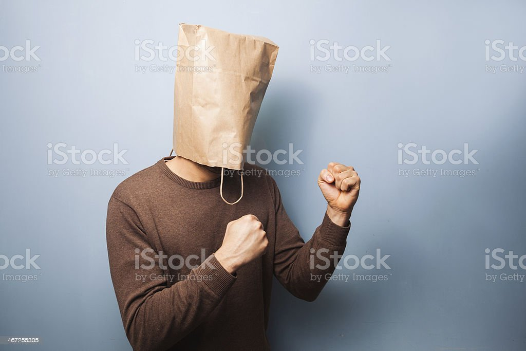 Young man with bag over his head in fighting stance stock photo