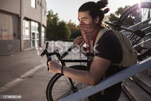 Close up of Young man with bandana carrying bike outdoors