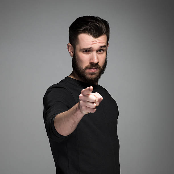 Young man with beard and mustaches, finger pointing towards the stock photo