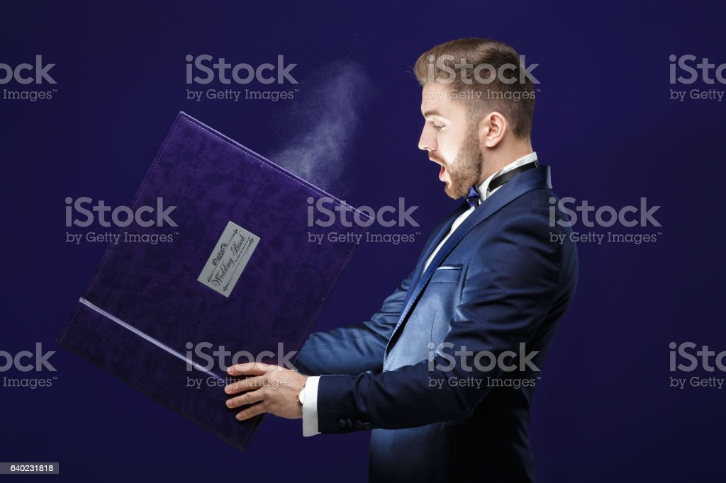 young man with beard holding book and magic light on stock photo