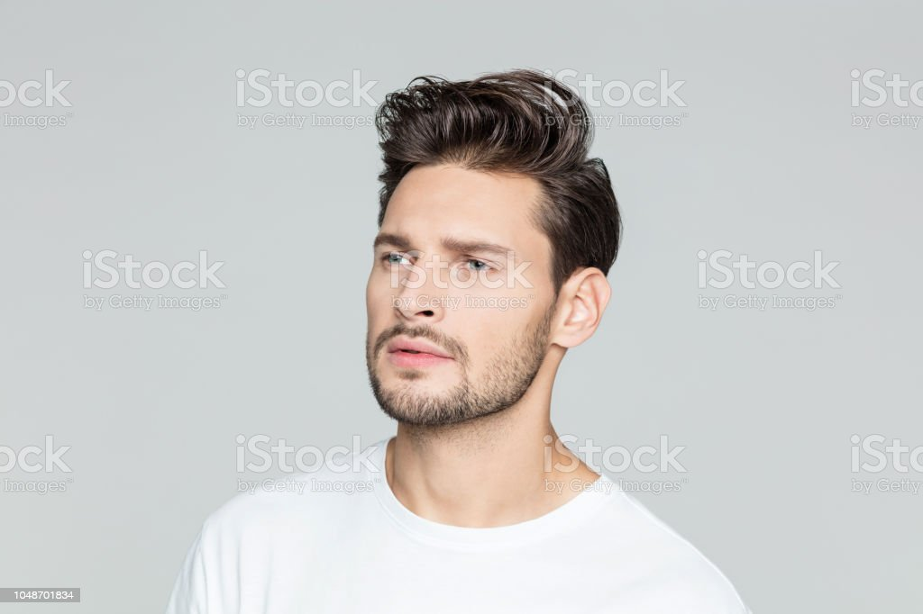 Young man with beard looking away at copy space Portrait of young man with beard looking away at copy space on grey background. 25-29 Years Stock Photo