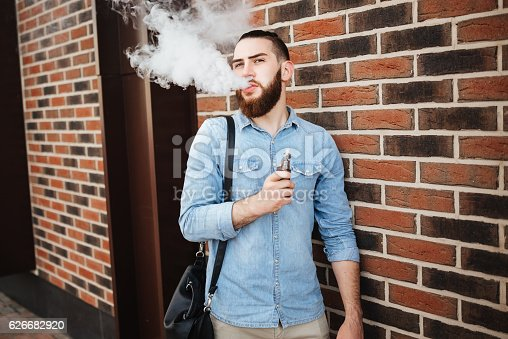 689660424 istock photo Young man with beard vaping an electronic cigarette outdoor. 626682920