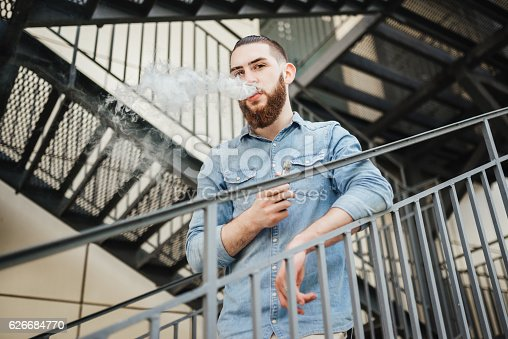 689660424 istock photo Young man with beard vaping an electronic cigarette outdoor. 626684770
