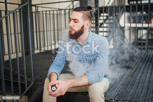 689660424 istock photo Young man with beard vaping an electronic cigarette outdoor. 626685040