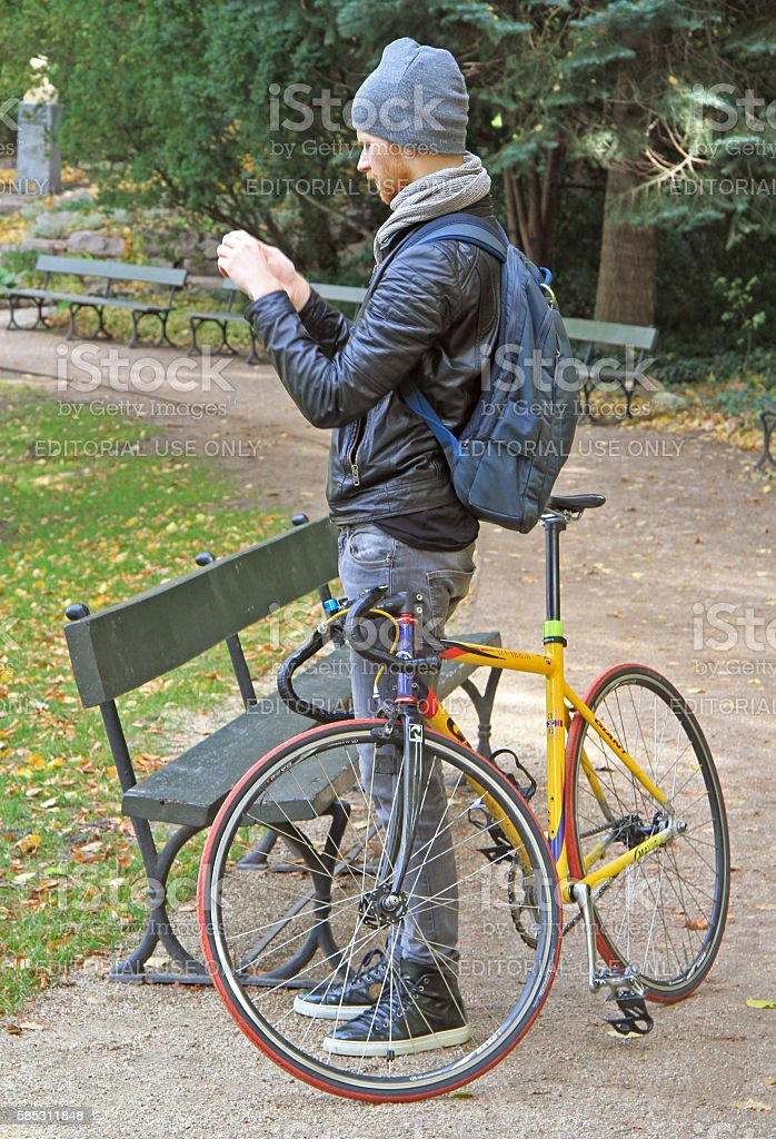 young man with bicycle is taking photo in park stock photo