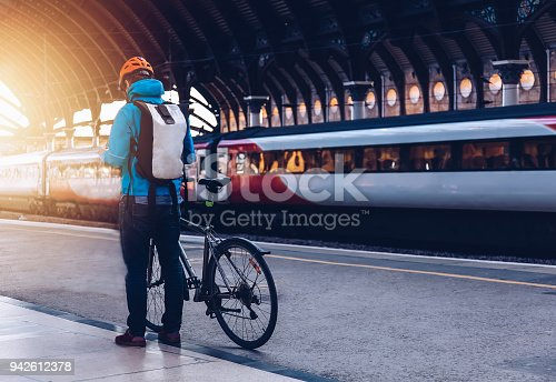 Young man who wearing helmet, is with bicycle on a public transport.