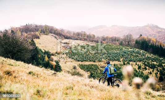 Young man with his bicycle walking up the hill outside in nature. Copy space.