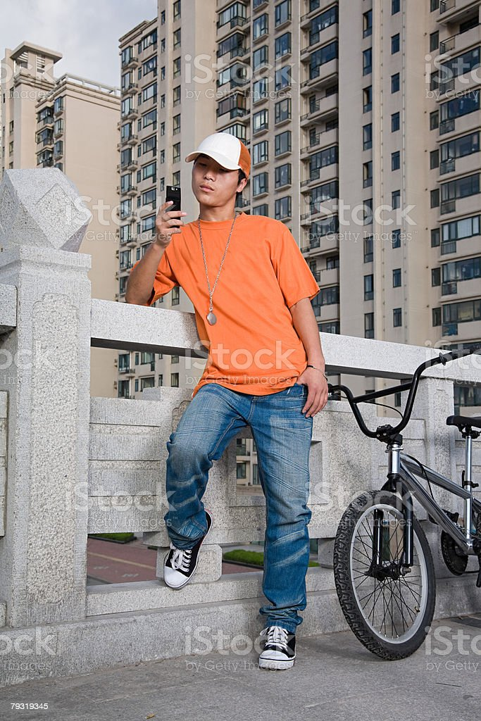 Young man with bike and cellphone 免版稅 stock photo