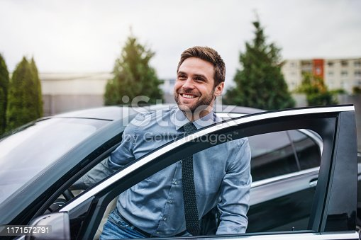 Happy young man with blue shirt and tie getting out of car in town.