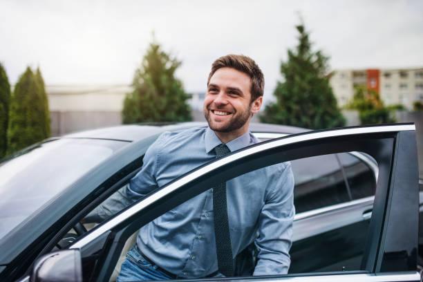 joven con camisa azul y corbata saliendo del coche en la ciudad. - conductor oficio fotografías e imágenes de stock