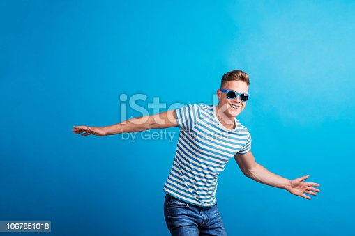A happy young man with blue sunglasses and striped T-shirt standing in a studio, having fun.